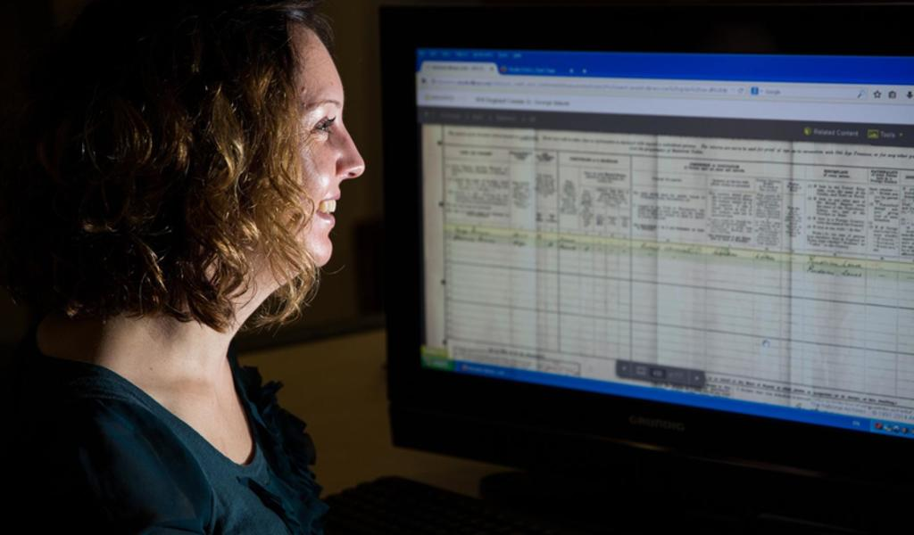 A researcher using a family history website on a computer