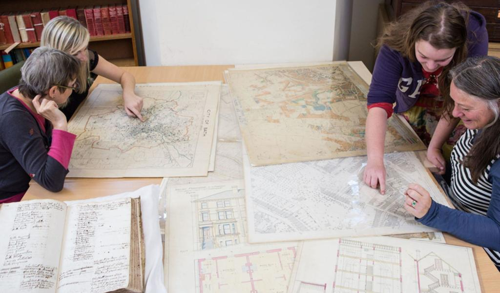A photograph of researchers examining maps in the Record Office.