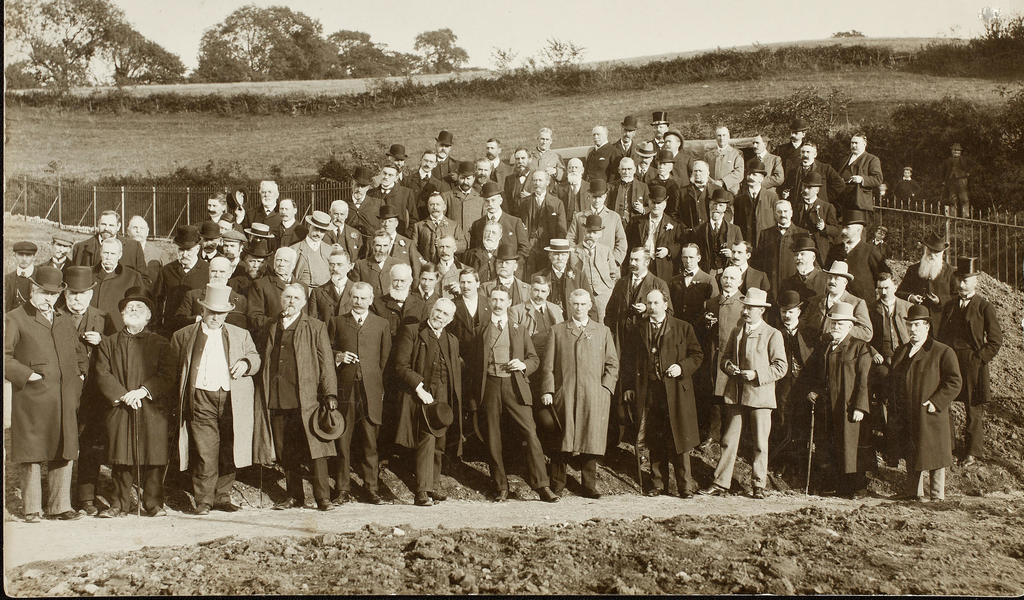 Photograph of a large group of civic dignitaries standing at the edge of a new reservoir
