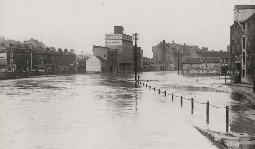 Black and white photograph of flooded area of Bath, with writing on the side of a building