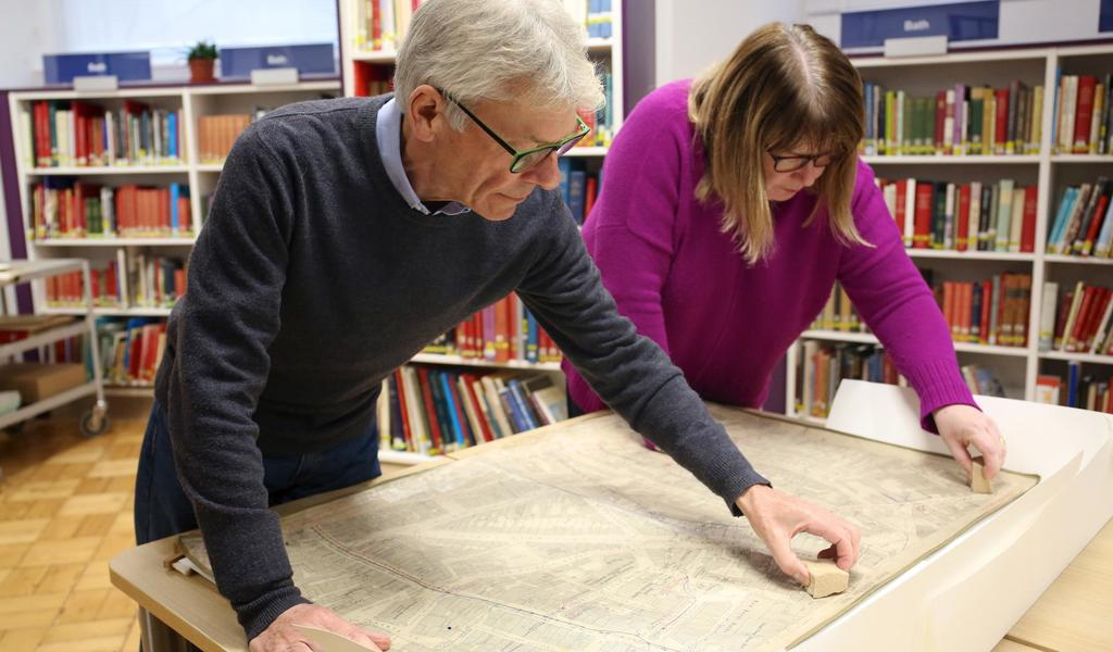 Volunteers cleaning maps as part of a cataloguing project