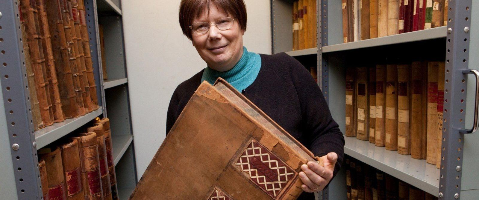 Photograph of an archivist in a strongroom, holding a large volume