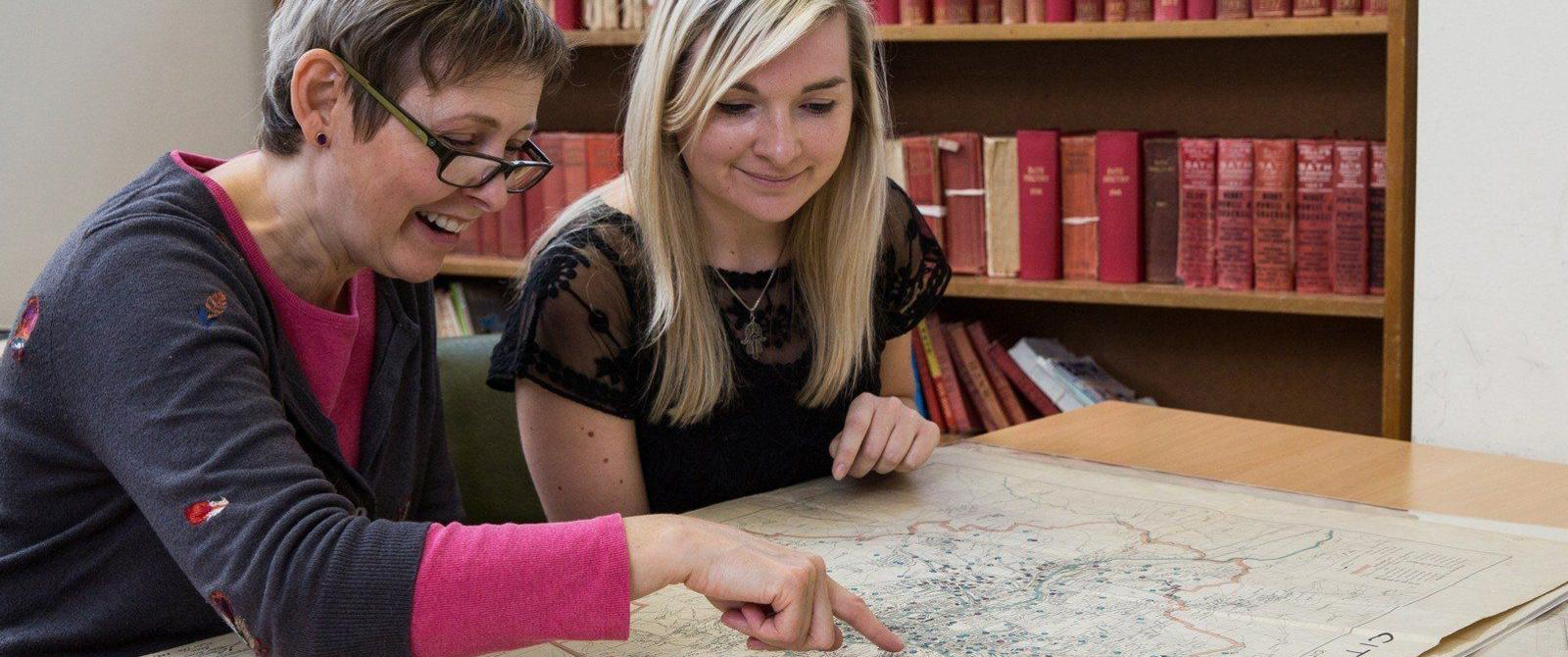 Two visitors in the Record Office searchroom looking at an old map.