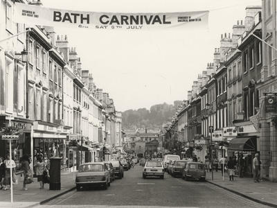 Photograph of Milsom Street with a Carnival banner, 1980s