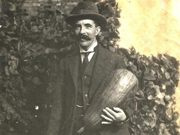 A sepia image of a man in a suit holding a potato and a large marrow