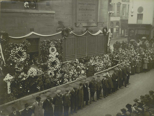 Black and white photo of people at Bath's War memorial with many floral tributes