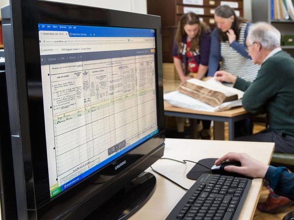 Photograph of  computer screen in the Record Office searchroom, with researchers in the background