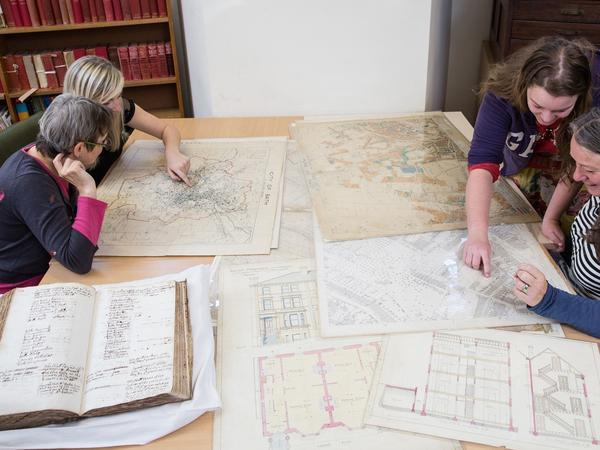 Photograph of researchers looking at maps and other records in the Record Office search room.
