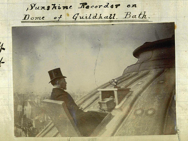 A man in a top hat takes sunshine readings on the roof of the Guildhall in Bath