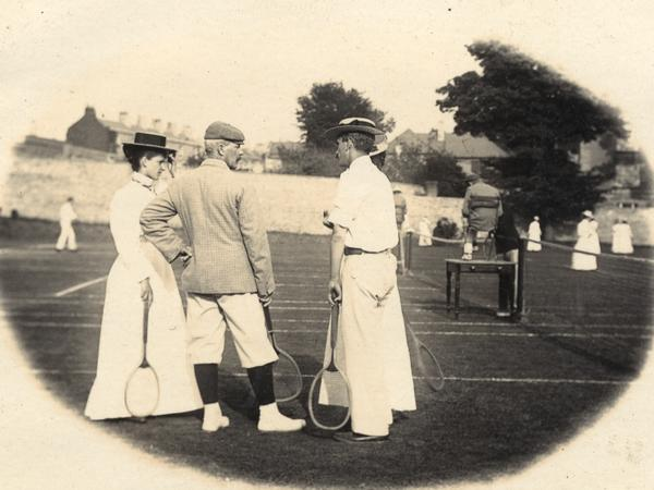 Sepia photograph of tennis players, the women in long skirts