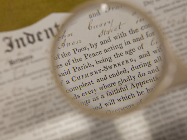 Part of an apprenticeship indenture seen through a magnifying glass