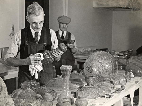 Black and white photograph of the Assembly Rooms chandeliers dismantled and being cleaned