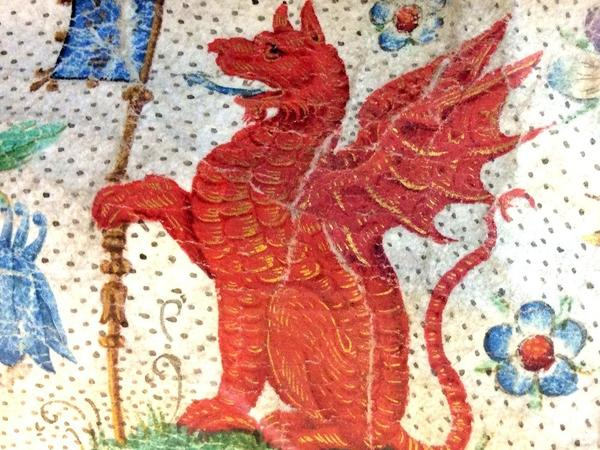 A red heraldic dragon sitting on its haunches holding a blue flag