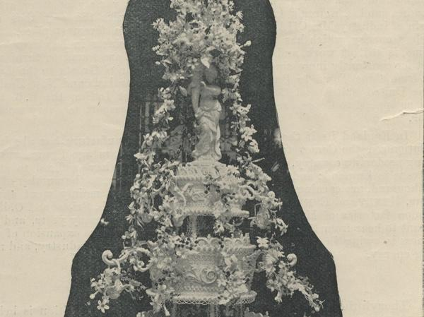Black and white photo of a mult-tiered wedding cake flowing with sugar-paste flowers