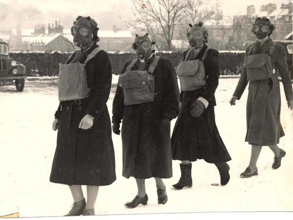 Black and white photo of four people wearing gas masks in the snow
