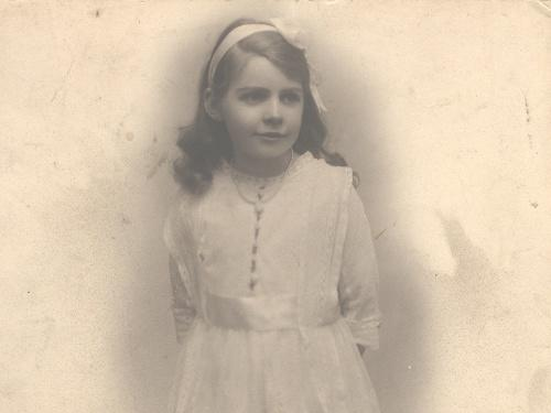 Black and white photograph of a young girl in a white lace party dress