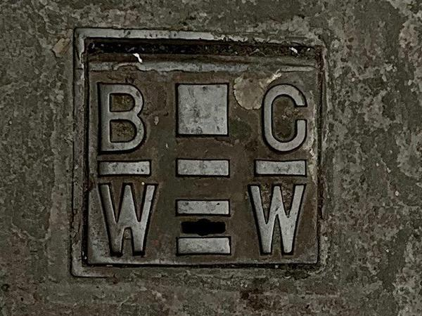 Photograph of a drain cover with the initials BCWW