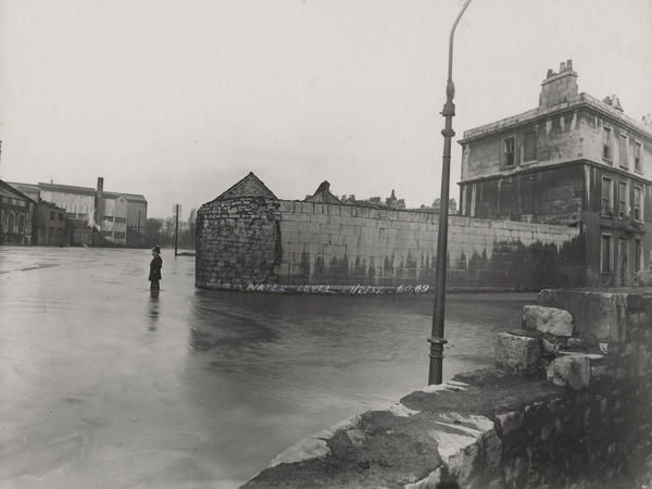 Black and white photograph of a policeman standing in flood water at the edge of the River Avon